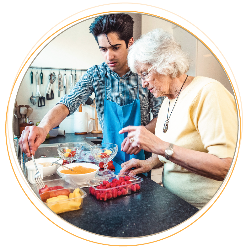 Young man helping and older woman sorting fruit in the kitchen